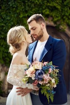 사랑 이야기 여자와 남자. 사랑하는 부부는 아름다운 부부를 포용합니다. 긴 고급스러운 가벼운 드레스에 재킷과 소녀의 남자