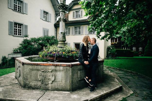 Любовная история. молодая влюбленная пара, целовать рядом с красивым фонтаном с цветами.