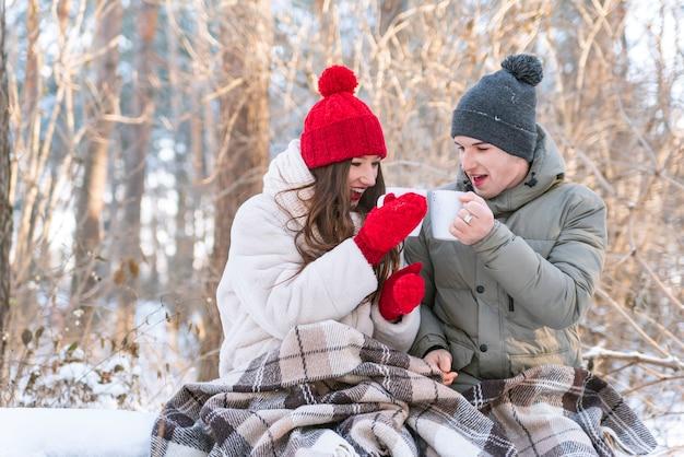 История о любви. молодая пара в зимнем парке завернута в одеяло и пьет чай.
