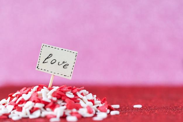 バレンタインデーのコンセプトのピンクの壁に赤と白のヒープのハートでボード上に構成された愛のテキスト。