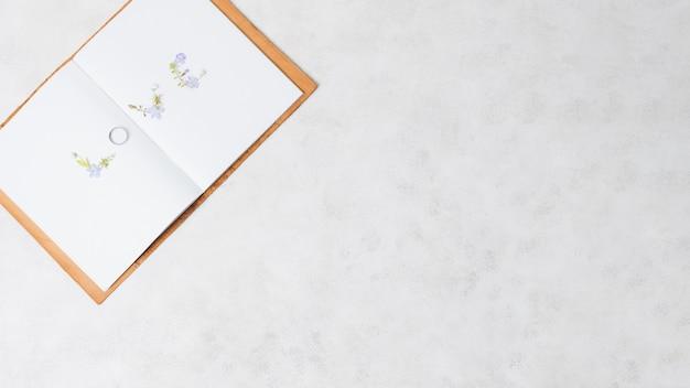 구체적인 배경 위에 열린 책에 결혼 반지로 만든 사랑 텍스트