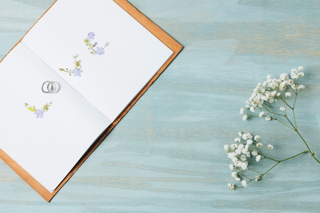 Love text made with wedding rings on an open book with gypsophila flower over wooden backdrop