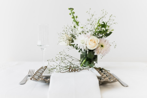 Love text on plate near bunch of flowers and wineglass on white table
