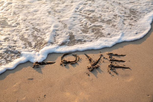 Love text on white sand beach