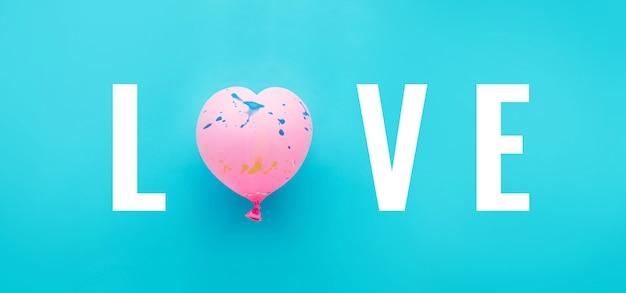 青い背景にピンクの風船のハートの形のテキストが大好き