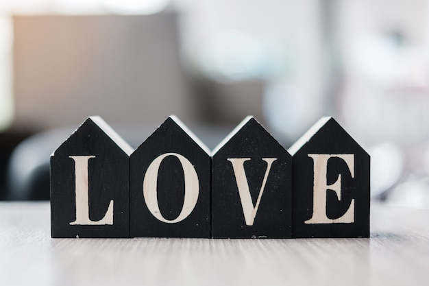 Love text with wooden home model  on table office. new house, financial, property, happy valentines day and real estate concepts