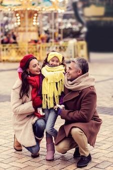 그들을 사랑해. 가족과 함께 걷는 동안 양성을 표현하는 놀라운 갈색 머리 여자