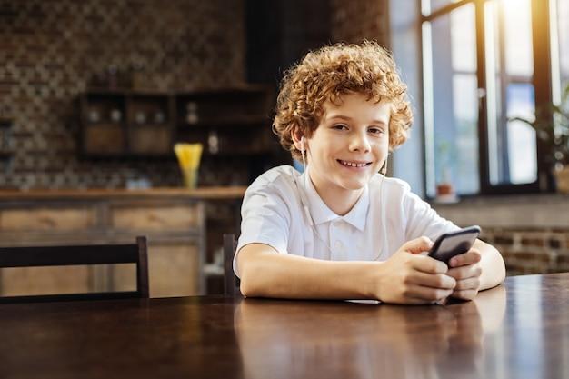 이 노래를 좋아한다. 편안하고 좋아하는 음악을 들으면서 그의 얼굴에 밝은 미소로 카메라를 찾고 곱슬 머리 소년의 초상화.