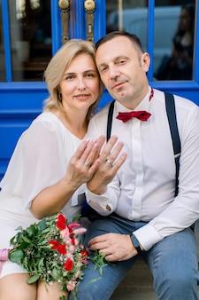 長年にわたる愛。幸せな笑顔の成熟したカップル、街の通りの青いヴィンテージのドアの前に座って、結婚指輪で彼らの手を示しています。顔に焦点を当てる