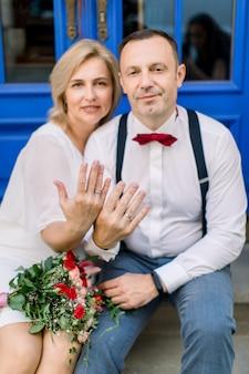 長年にわたる愛。幸せな笑顔の成熟したカップル、街の通りの青いヴィンテージのドアの前に座って、結婚指輪で彼らの手を示しています。リングに焦点を当てる
