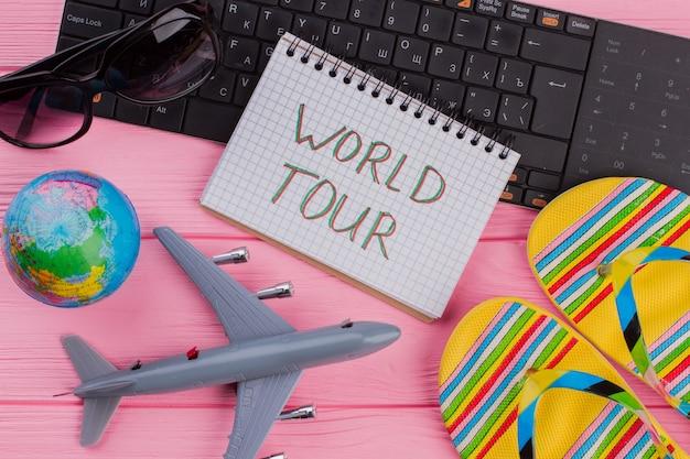 女性の旅行者のアクセサリーのメガネの財布とピンクのテーブルのフリップフロップとノートブックのツアーが大好きです...
