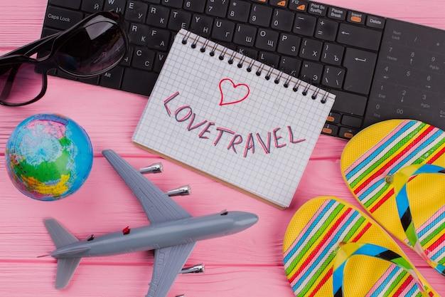 ピンクのテーブルに女性の旅行者のアクセサリーメガネ財布とフリップフロップとノートブックの旅行が大好きです...