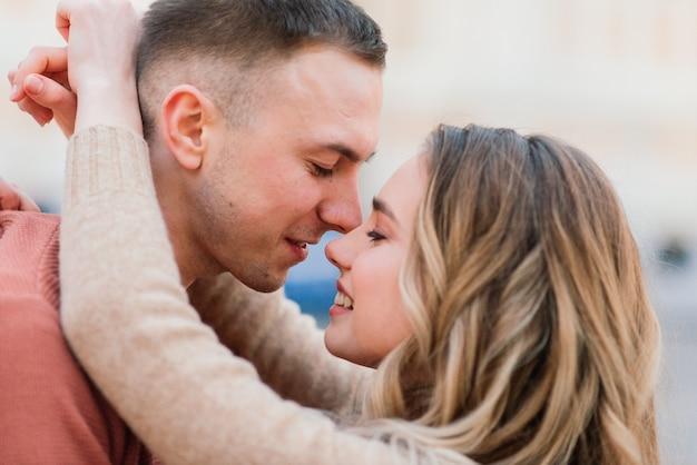 愛、旅行、観光、関係、デートのコンセプト-通りで抱き締めるロマンチックな幸せなカップル。聖バレンタインの休日