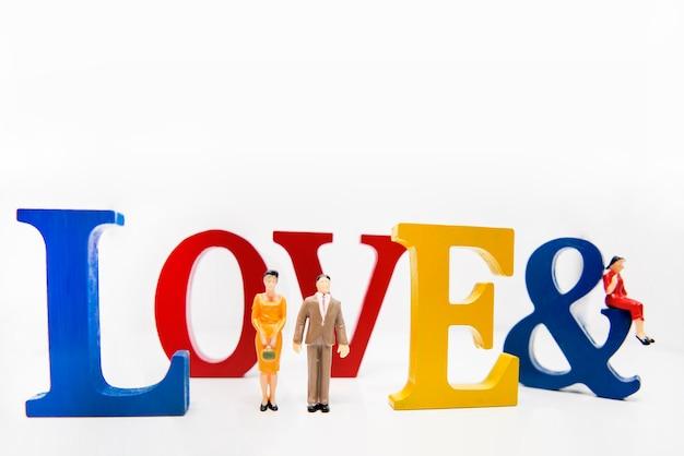 Любовный треугольник. абстрактное фото любви и влюбленных. большие деревянные буквы с маленькими пластиковыми фигурками людей.