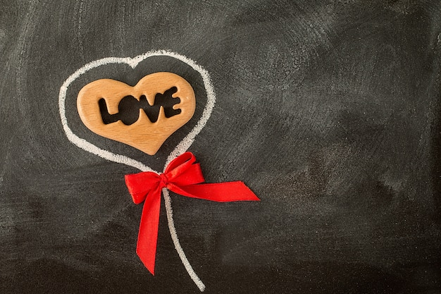 Love valentine heart and red bow on the chalkboard