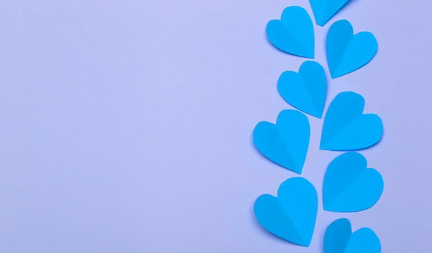 Love (valentine's day) background or wedding background. blue paper hearts on a purple pastel background. love concept