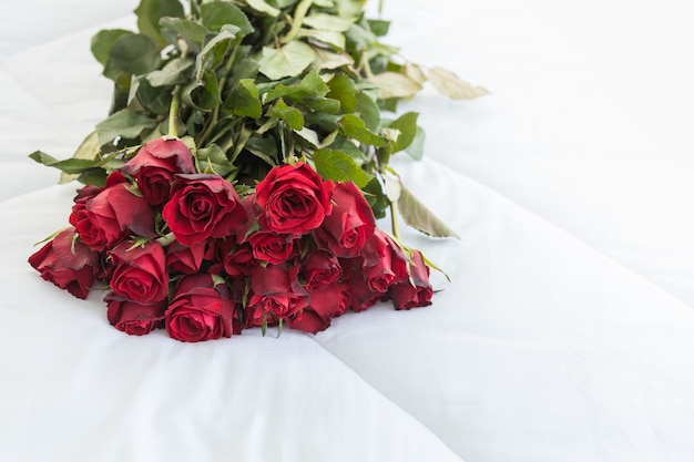 Love and valentine's day concept. close up of red roses bouquet on white bed