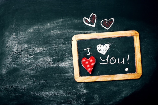 Love or valentine's day concept with chalkboard and hearts on a