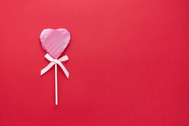 愛、バレンタインデーのモックアップ、フラットレイアウト、赤い背景、コピースペースに分離されたハートの形をしたピンクのロリポップ。