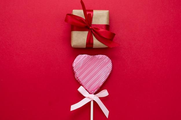 Любовь, день святого валентина макет, с леденец в форме сердца и подарочные boxex, изолированных на красном фоне, копией пространства.