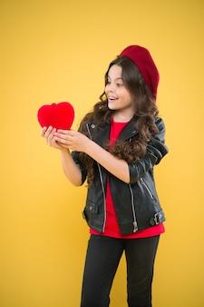 사랑. 발렌타인 데이. 노란색 벽에 아이입니다. 긴 곱슬 머리를 가진 작은 여자 아이. 프랑스 베레모와 가죽 재킷을 입은 행복한 소녀. 파리 패션 소녀는 붉은 마음을 잡아. 세계 심장의 날. 사랑과 로맨스.