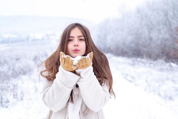 冬が大好きです。赤い唇を吹く幸せなクールな女の子は、雪の背景の上に白いセーターを着てエアキスをします。