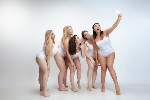 Innamorato di me stesso. ritratto di belle giovani donne plus size in posa sul bianco
