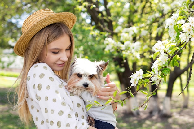 Love between woman and her dog, woman hugs her yorkshire terrier