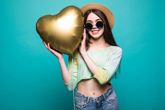 黄金のハート型のバルーンを保持している笑顔の女性が大好きです。緑に分離された愛のかわいい美しい若い女性