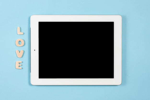 Love wooden text near the digital tablet with black screen display on blue background