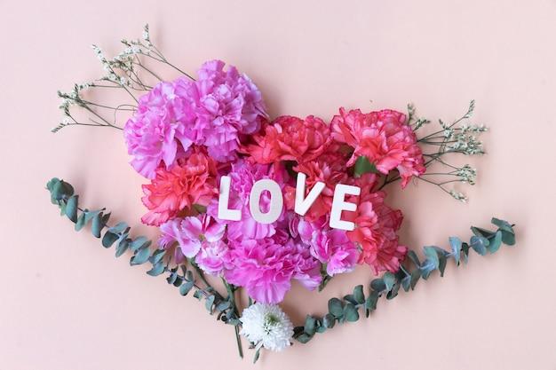 Love wooden word on fresh carnation flowers bouquet