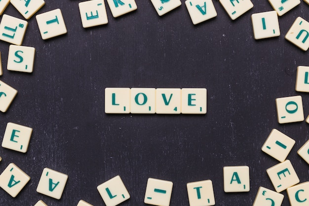 Love word arranged on black background surrounded by scrabble letters