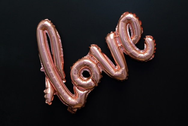 Love word from pink inflatable balloon on black isolated on black