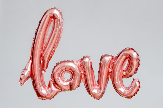 Love word from pink inflatable balloon floating in the air