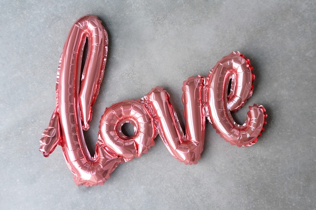 Love word from pink inflatable balloon on grey concrete background. the concept of romance, valentine's day. love rose gold foil balloon