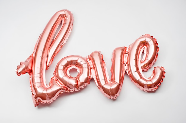 Love word from pink inflatable balloon on white