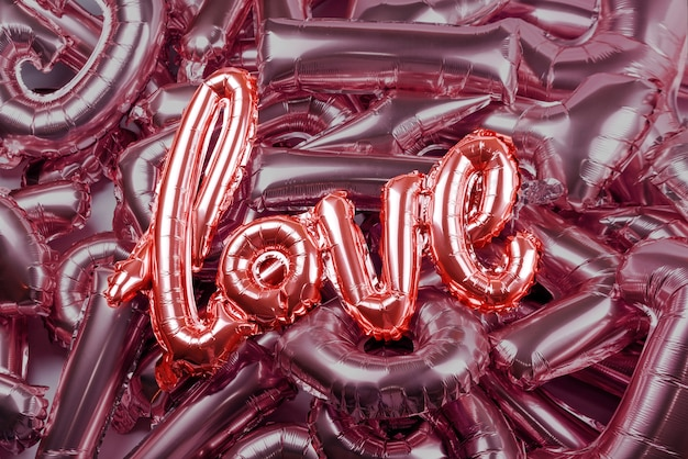 Love word from pink inflatable balloons laying on other letters made of balloons, concept of romance, valentine's day