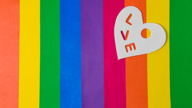 Love word on heart over bright lgbt flag