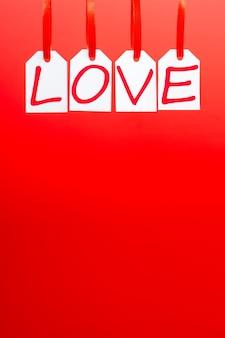 Слово любви написано белыми ярлыками на красном фоне.