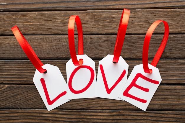 Слово любви написано в белых метках на деревянном фоне.