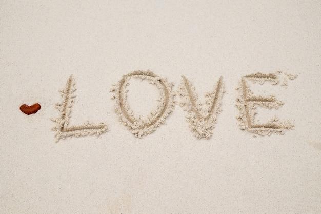 해변 하얀 모래에 작성하는 사랑. 빈티지 톤, 복고풍 필터 효과, 소프트 포커스, 낮은 빛. (선택적 초점)
