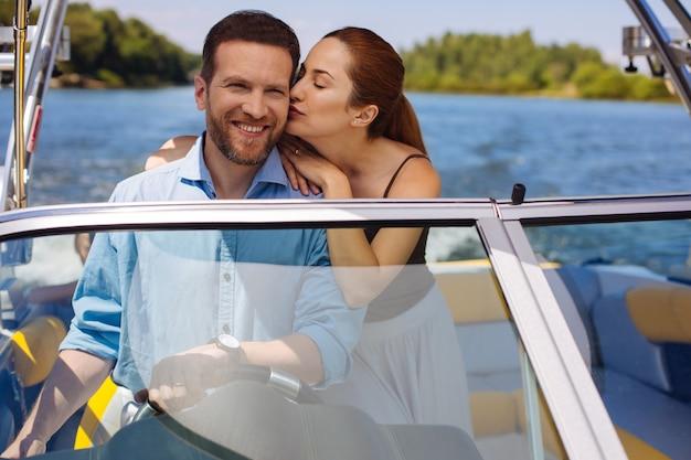 あなたを愛してます。愛情のこもった若い女性は、夫がボートを航海して笑っている間、頬にキスをします