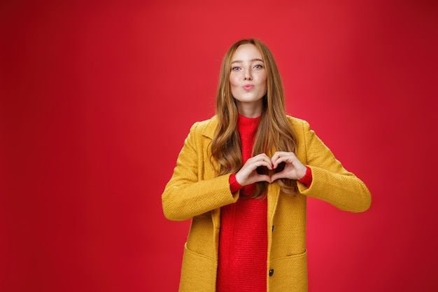 Love you all. portrait of romantic and stylish good-looking flirty redhead female with freckles and blue eyes folding lips to give kiss showing heart gesture, confessing in sympathy over red wall.
