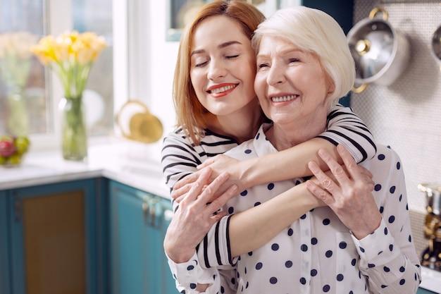 あなたを愛してます。魅力的な年配の女性が年配の母親に背中を抱きしめ、喜びで目を閉じ、台所に立っている間幸せに笑っている