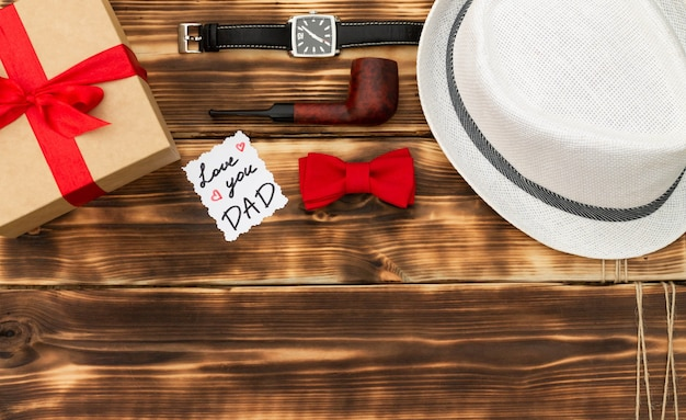 Love you dad greeting card with a gift box and men's accessories on a rustic wooden tabletop