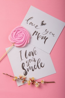Love you mom  handwritten inscription. hand drawn lettering,  calligraphy. card with spring tree brunch background, valentine, mother's day.