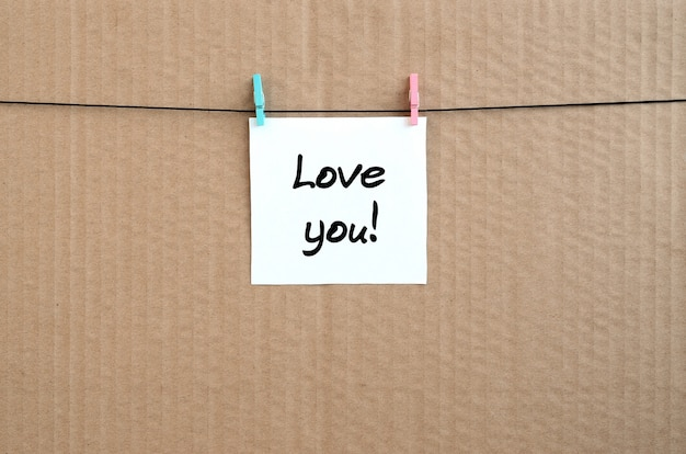 Love you! note is written on a white sticker that hangs with a clothespin on a rope on a background of brown cardboard