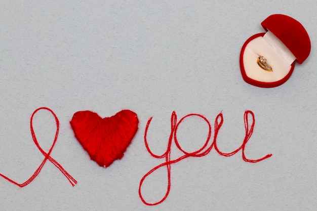 あなたのバレンタインデーのために分離された赤い糸で作られた言葉とハートのシンボルを愛してください