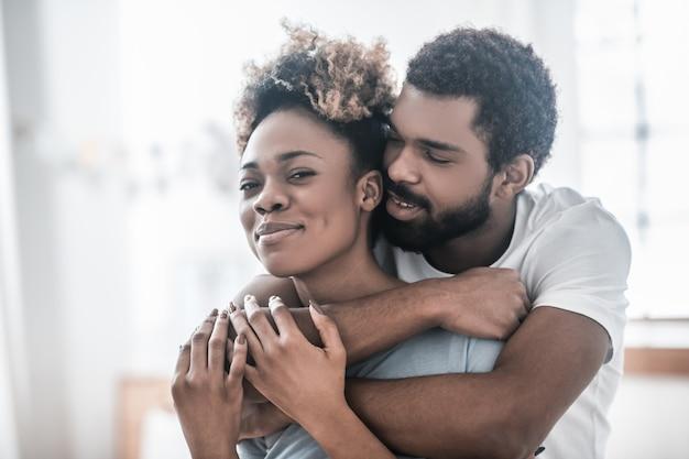 Любовь. молодой бородатый афроамериканец нежно обнимает счастливую улыбающуюся женщину, стоящую дома днем