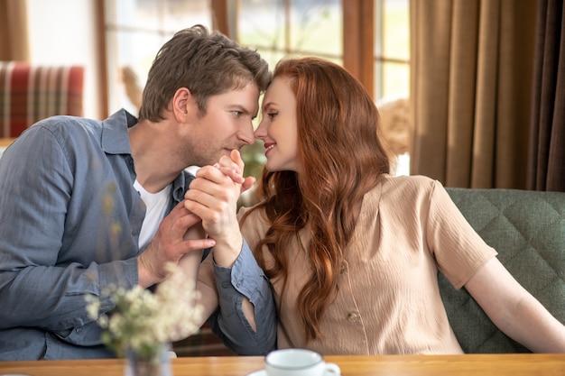 Любовь. молодые счастливые взрослые мужчина и женщина сидят рядом, нежно смотрят друг на друга в ресторане днем